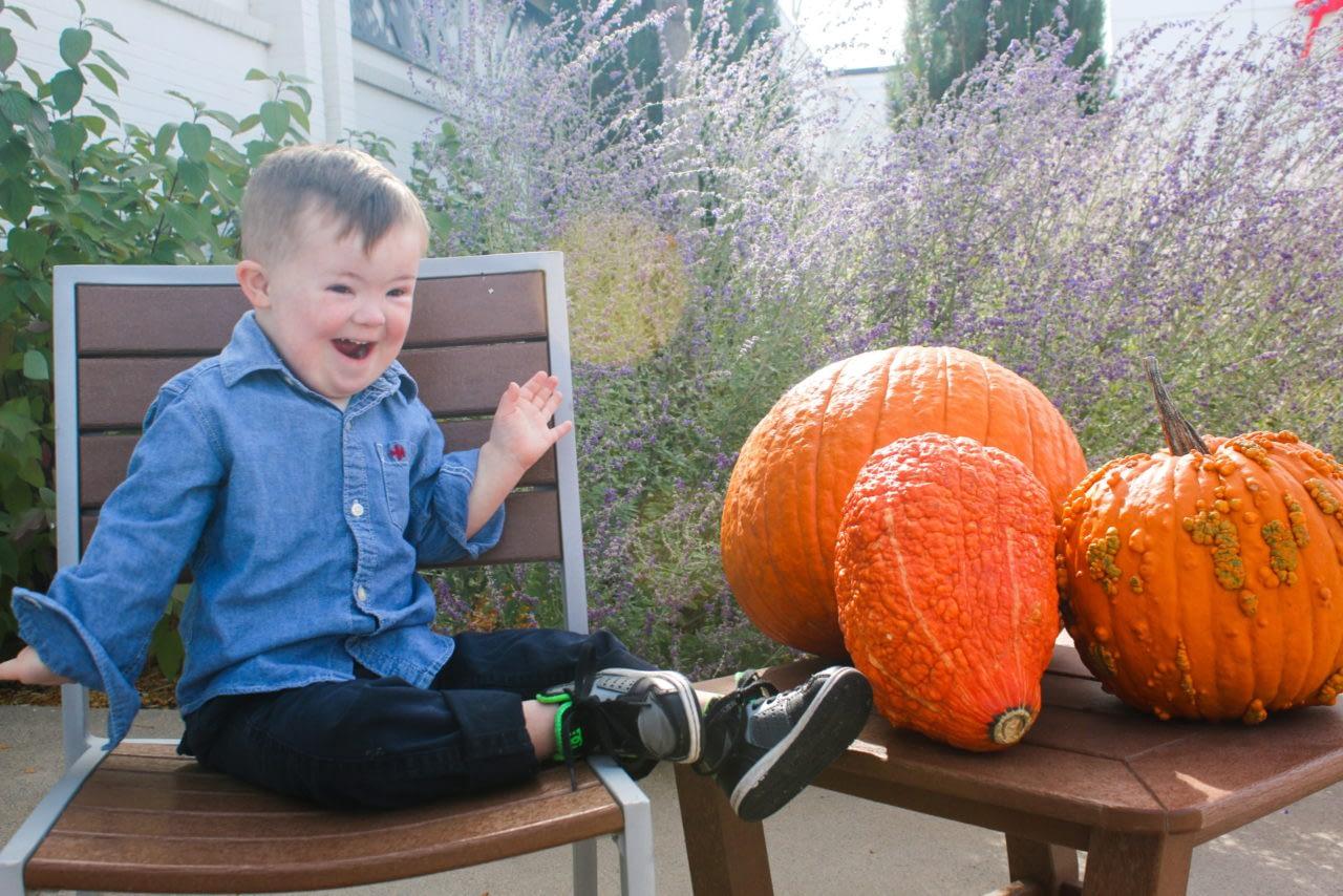 Special needs boy looking at pumpkins